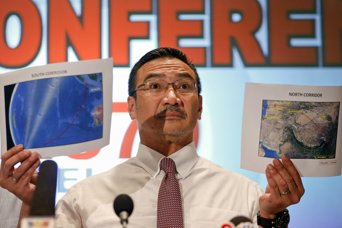 Malaysia's acting Transport Minister Hishammuddin Hussein shows two maps with corridors of the last known possible location of the missing Malaysia Airlines MH370