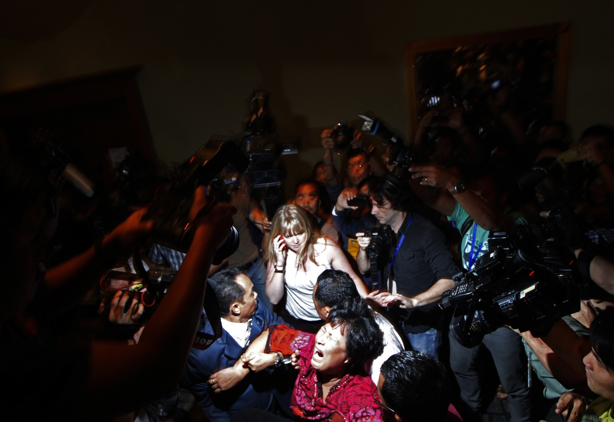 A Chinese family member of a passenger onboard the missing Malaysia Airlines Flight MH370 screams as she is being brought into a room outside the media conference area at a hotel in Kuala Lumpur International Airport