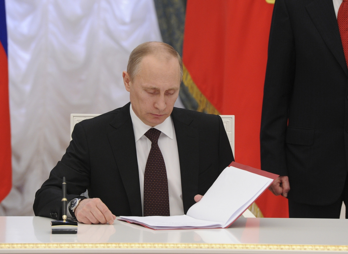 Russian President Vladimir Putin prepares to sign a law on ratification of a treaty making Crimea part of Russia