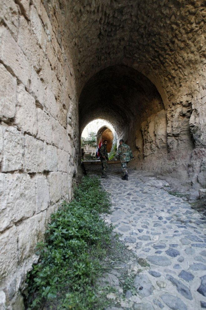 Soldiers loyal to Syria's President Bashar al-Assad walk inside the Krac des Chevaliers fortress in Homs countryside, after taking control of it from rebel fighters.