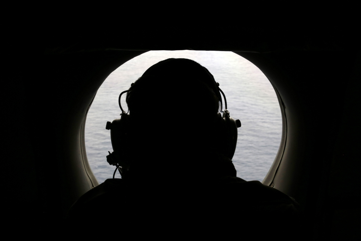 A crew member from a Royal New Zealand Airforce plane scans the Indian ocean for debris from missing Flight MH370.
