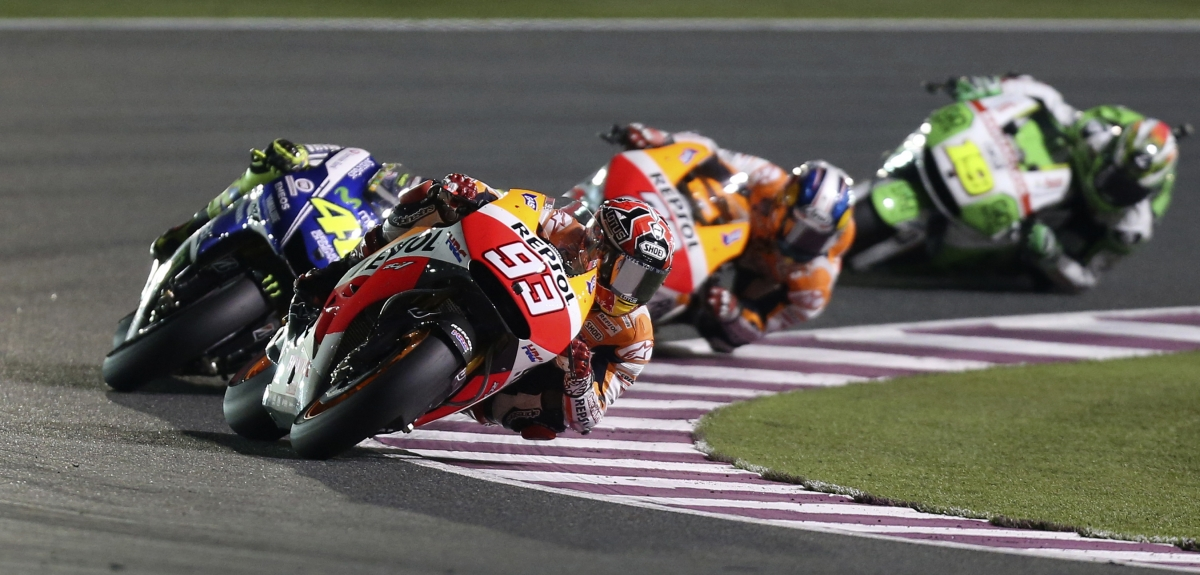 Honda MotoGP rider Marc Marquez (front) of Spain races ahead of Yamaha MotoGP rider Valentino Rossi (L) of Italy during the Qatar MotoGP Grand Prix at the Losail International circuit in Doha March 23, 2014.