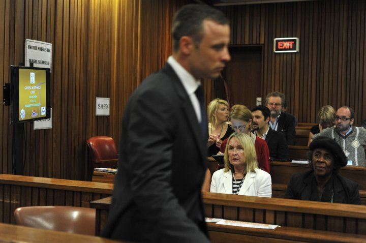 June Steenkamp (in white) watches Oscar Pistorius walk to the dock at his trial for killing Reeva Steenkamp