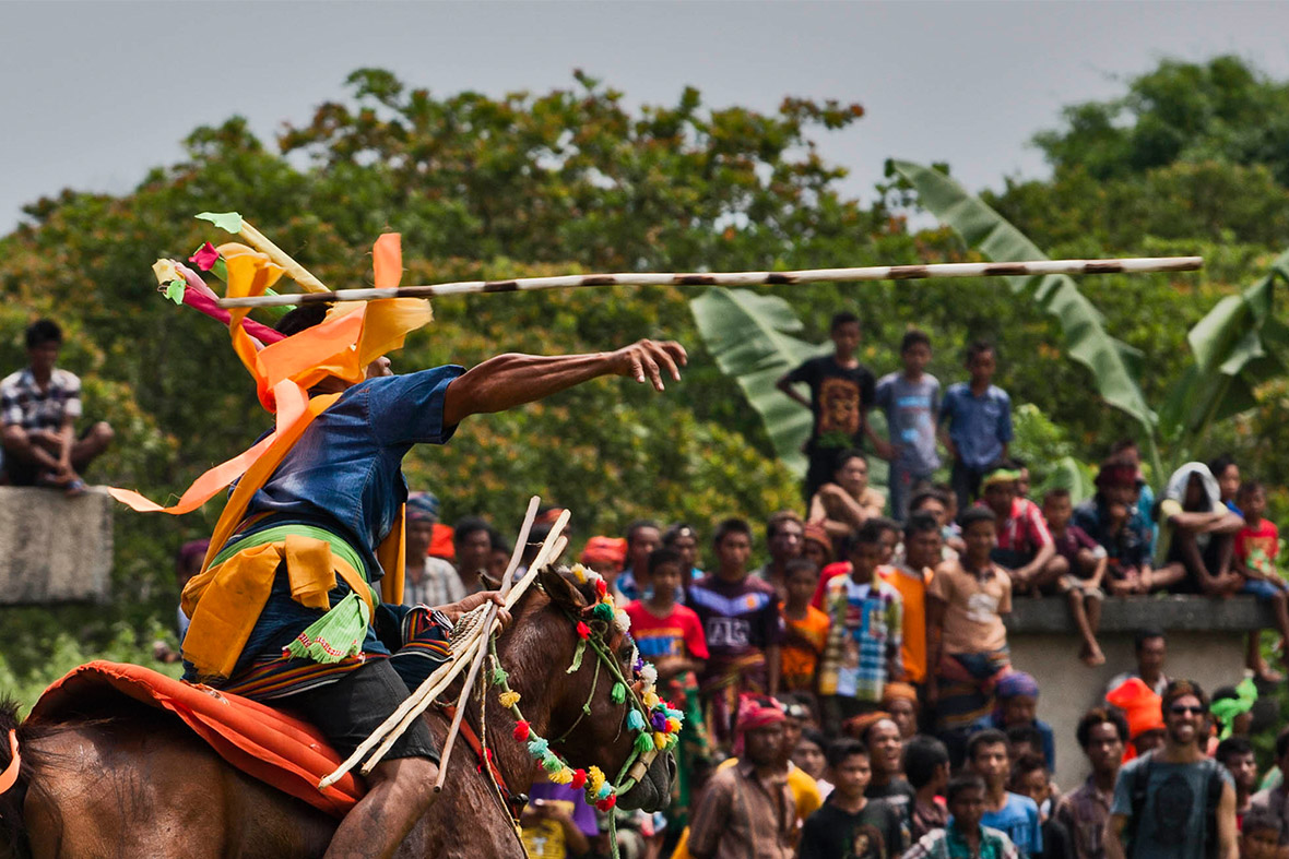 A Pasola rider throws his spear