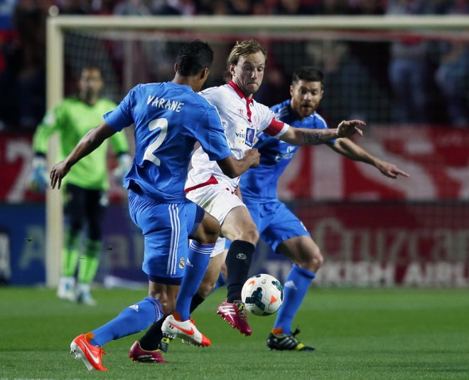 Sevilla's Ivan Rakitic (C) is challenged by Real Madrid's Xabi Alonso (R) and Raphael Varane during their Spanish First Division soccer match at Ramon Sanchez Pizjuan stadium in Seville, March 26, 2014.