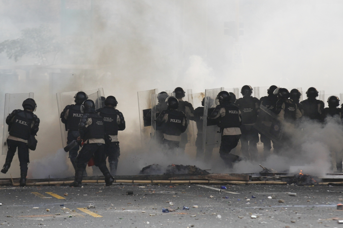Venezuela's national police officers stand amidst teargas during an opposition protest at Prados del Este's highway in Caracas
