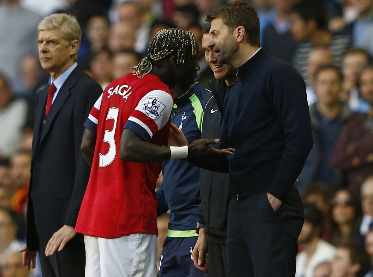 Arsenal's Bacary Sagna (L) reacts after he was hit by a ball thrown by Tottenham Hotspur's manager Tim Sherwood (R) during their English Premier League soccer match at White Hart Lane in London, March 16, 2014.