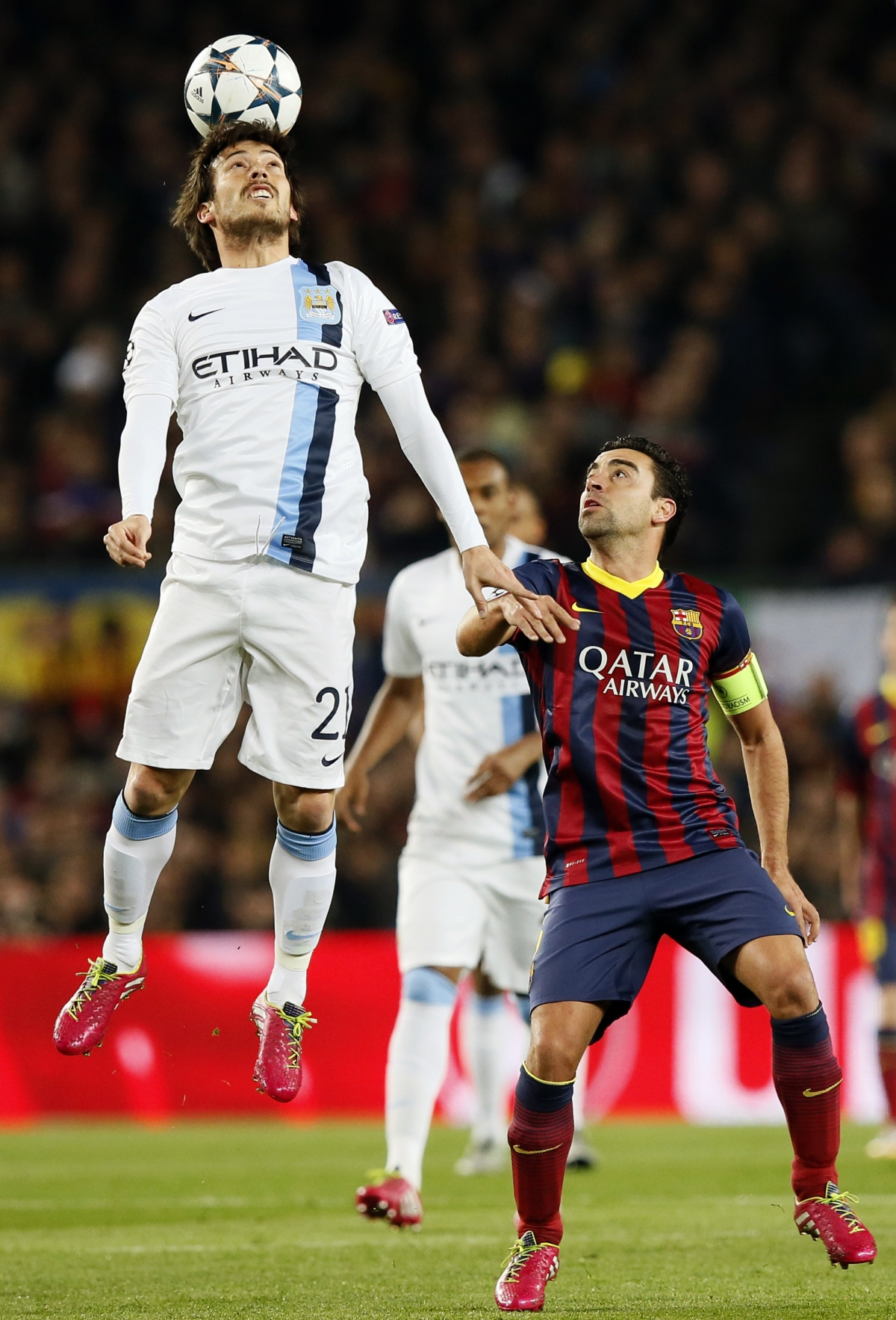 Manchester City's David Silva (L) heads the ball next to Barcelona's Xavi during their Champions League last 16 second leg soccer match at Camp Nou stadium in Barcelona March 12, 2014.