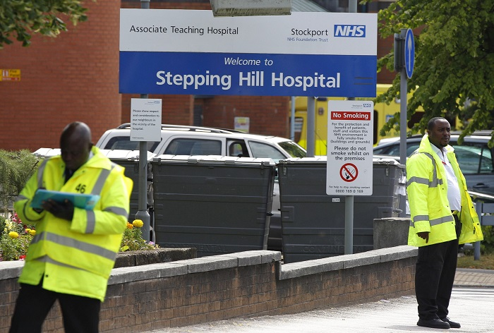 Guards patrol the entrance to Stepping Hill Hospital in Greater Manchester, where eight people died after being deliberately poisoned.