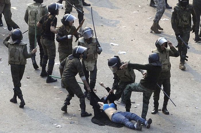 Egyptian army soldiers violently arrest a female protester during clashes in Tahiri Square in Cairo.