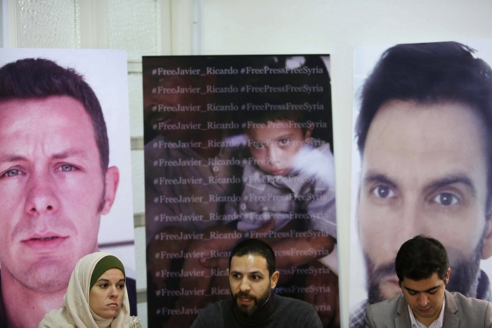 Monica Prieto (Left) wife of Spanish journalist Javier Espinosa sits at a press conference in front of images of Espinosa and photographer Ricardo Garcia Vilanova.