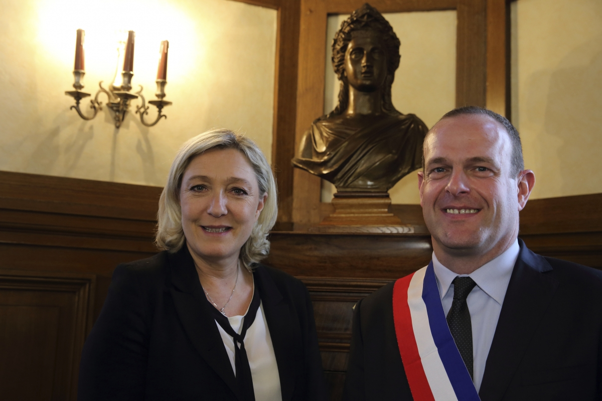 Steeve Briois (R), the new Mayor of Henin-Beaumont, wears his mayoral tricolour sash as he poses with Marine Le Pen, France's far-right National Front political party leader,