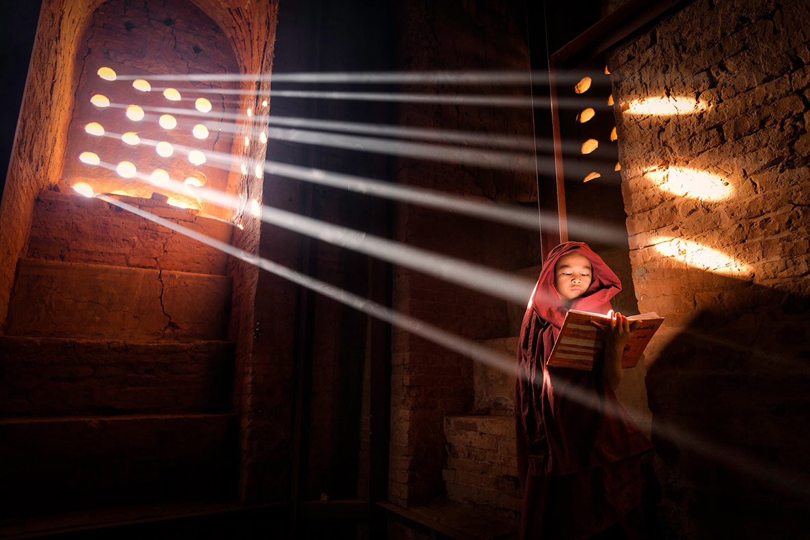 Young monk finds a perfect light source to read his book inside his pagoda in Old Bagan, Burma