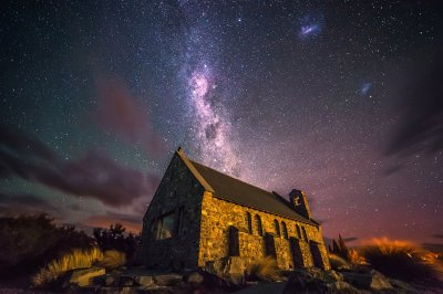 A dramatic night sky behind a little church in Tekapo, New Zealand