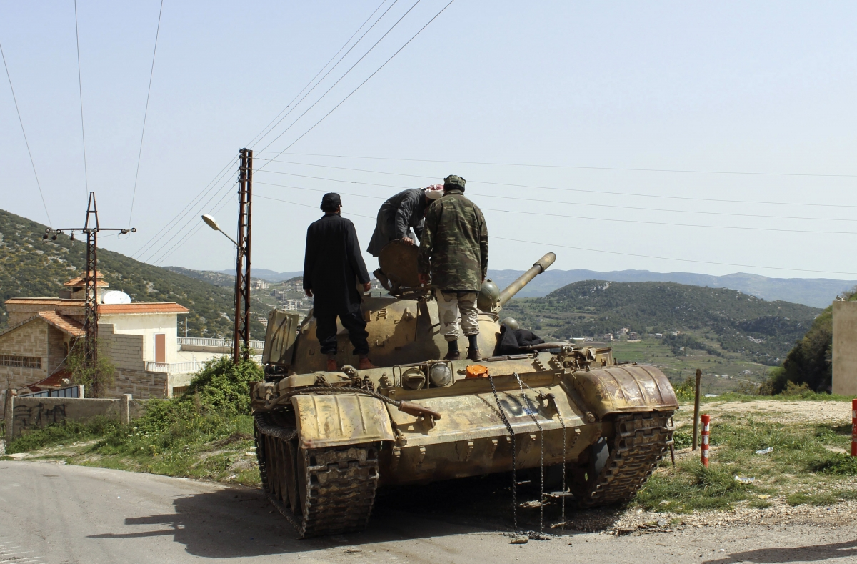 Free Syrian Army fighters stand on a tank at the Armenian Christian town of Kasab