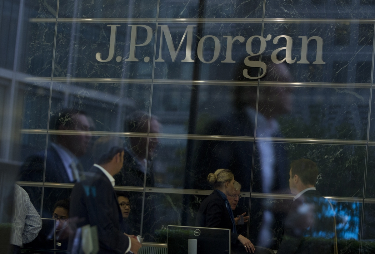 Workers are reflected in the windows of the Canary Wharf offices of JP Morgan