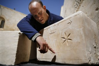 Israeli archeologist Eitan Klein of the Antiquities Theft Prevention Unit points at an engraved detail on one of the 11 ancient coffins containing Jewish bones from the Second Temple period