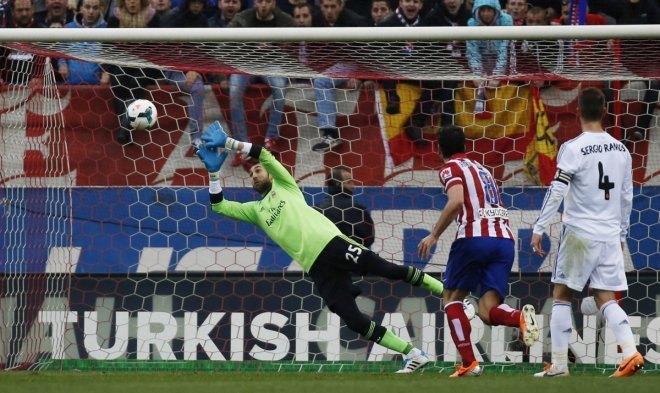 Real Madrid's goalkeeper Diego Lopez (L) fails to save a shot from Ateltico Madrid's Gabi Fernandez (unseen) during their Spanish first division soccer match at Vicente Calderon stadium in Madrid March 2, 2014.