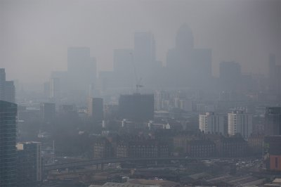 The Canary Wharf financial district is dimly seen through the smog blanketing London