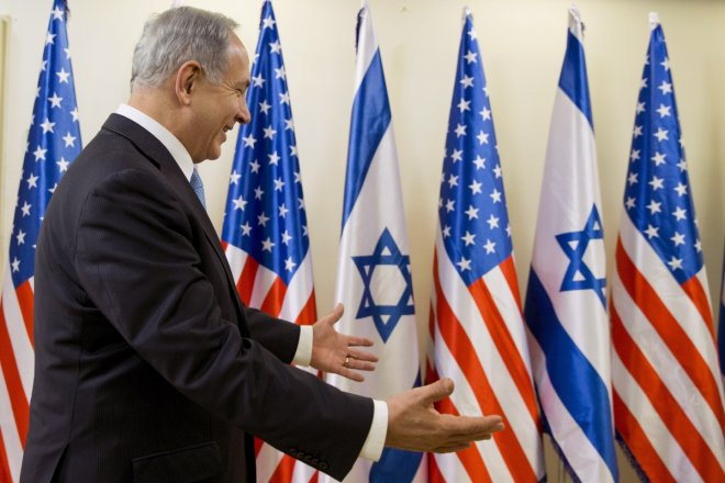 Israeli Prime Minister Benjamin Netanyahu gestures in welcome as U.S. Secretary of State John Kerry arrives for their meeting in Jerusalem