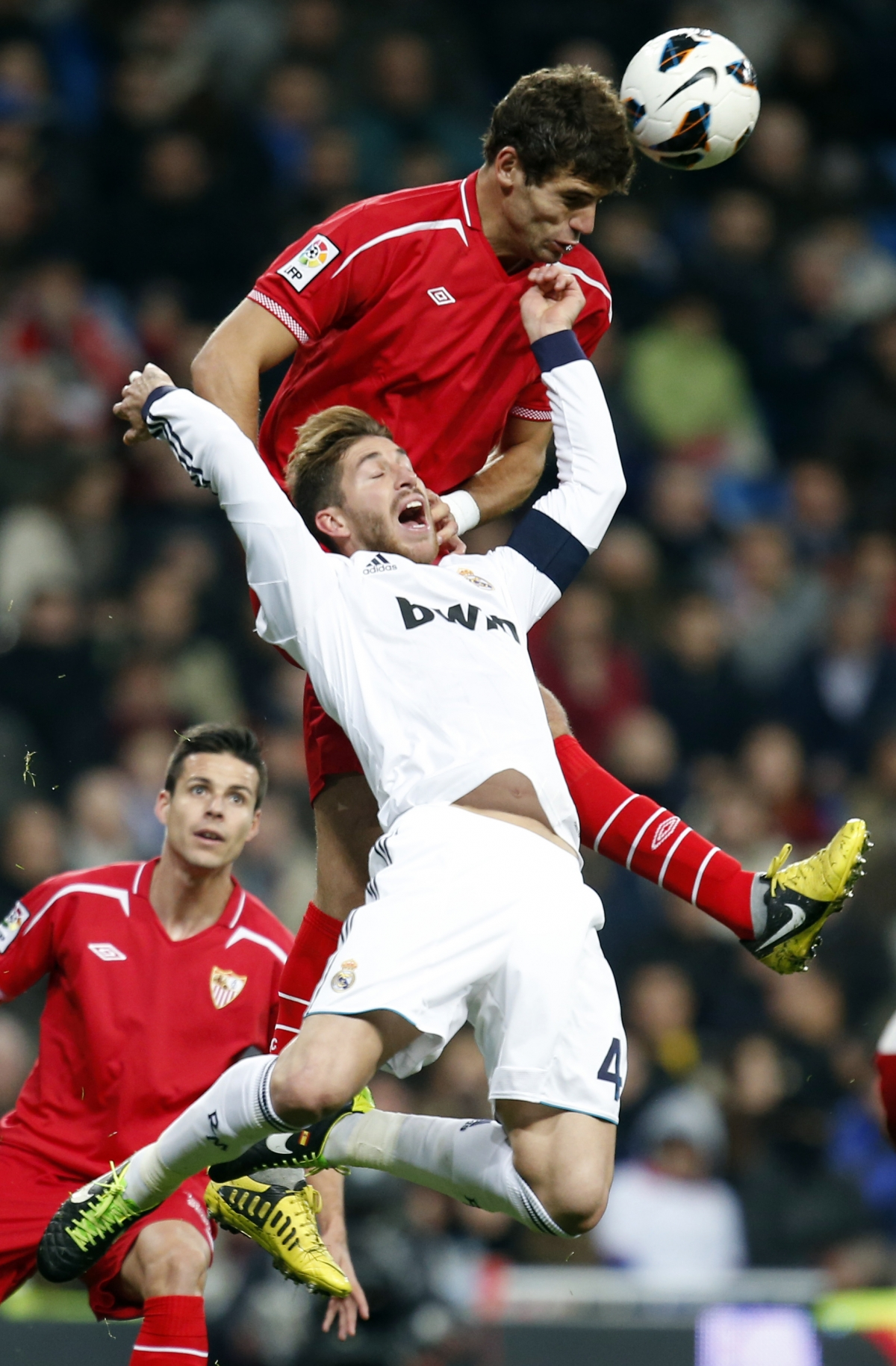 Real Madrid's Sergio Ramos (bottom) and Sevilla's Federico Fazio challenge for the ball during their Spanish first division soccer match at Santiago Bernabeu stadium in Madrid February 9, 2013.