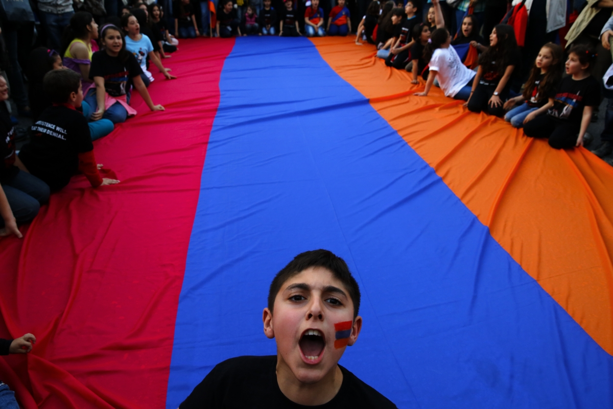An Armenian boy shouts slogans against Turkey in front of a huge Armenian flag during a demonstration near the Turkish embassy in central Athens