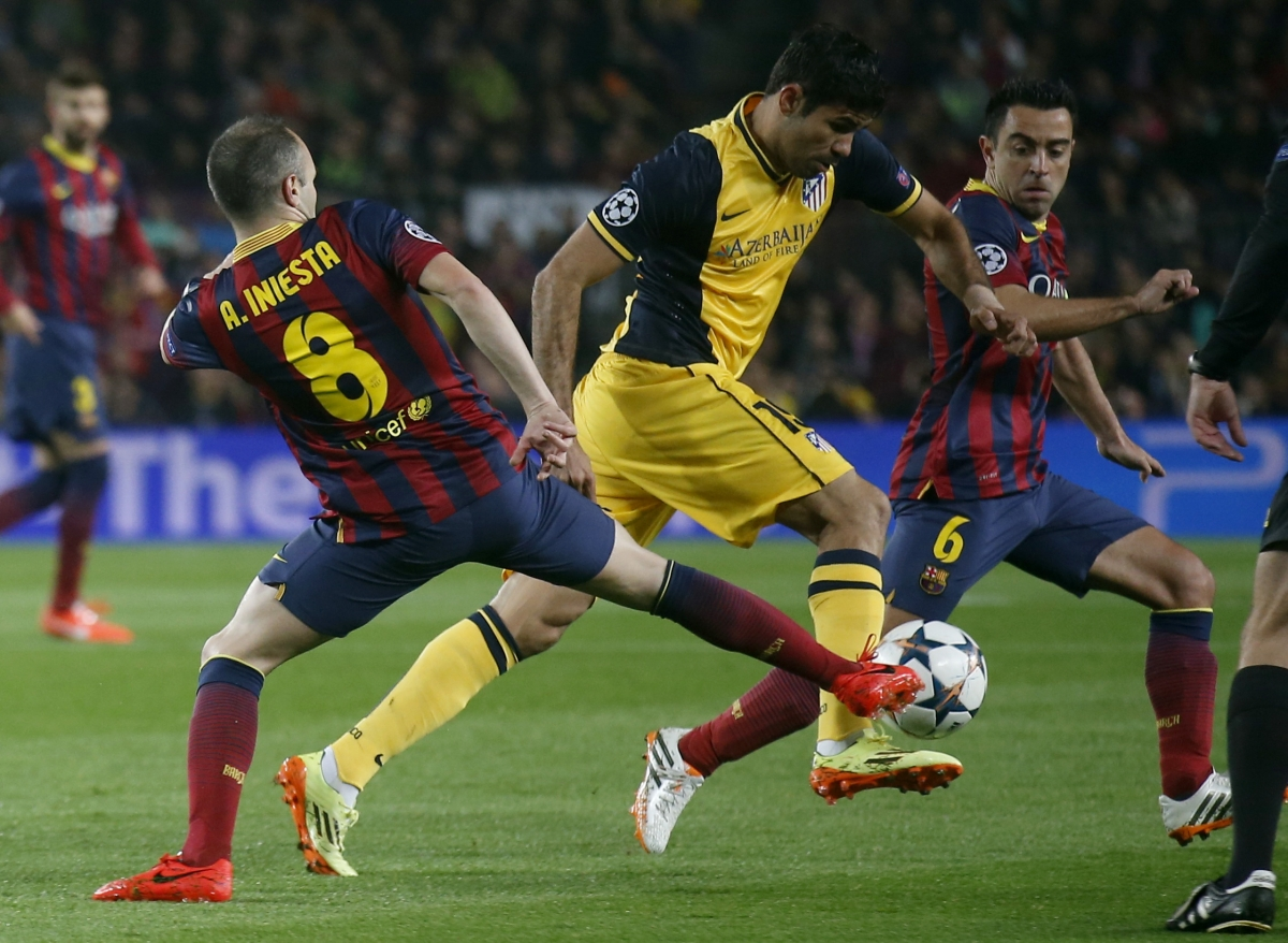 Atletico Madrid's Diego Costa (C) is challenged by Barcelona's Andres Iniesta (L) and Xavi during their Champions League quarter-final first leg soccer match at Camp Nou stadium in Barcelona April 1, 2014.