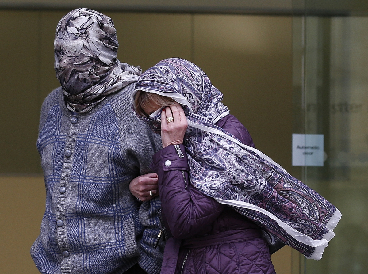 Randacore, face covered, leaves Westminster Magistrates Court with his wife in March.