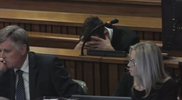 Oscar Pistorius holds his head in his hands as his trial resumes for killing Reeva Steenkamp