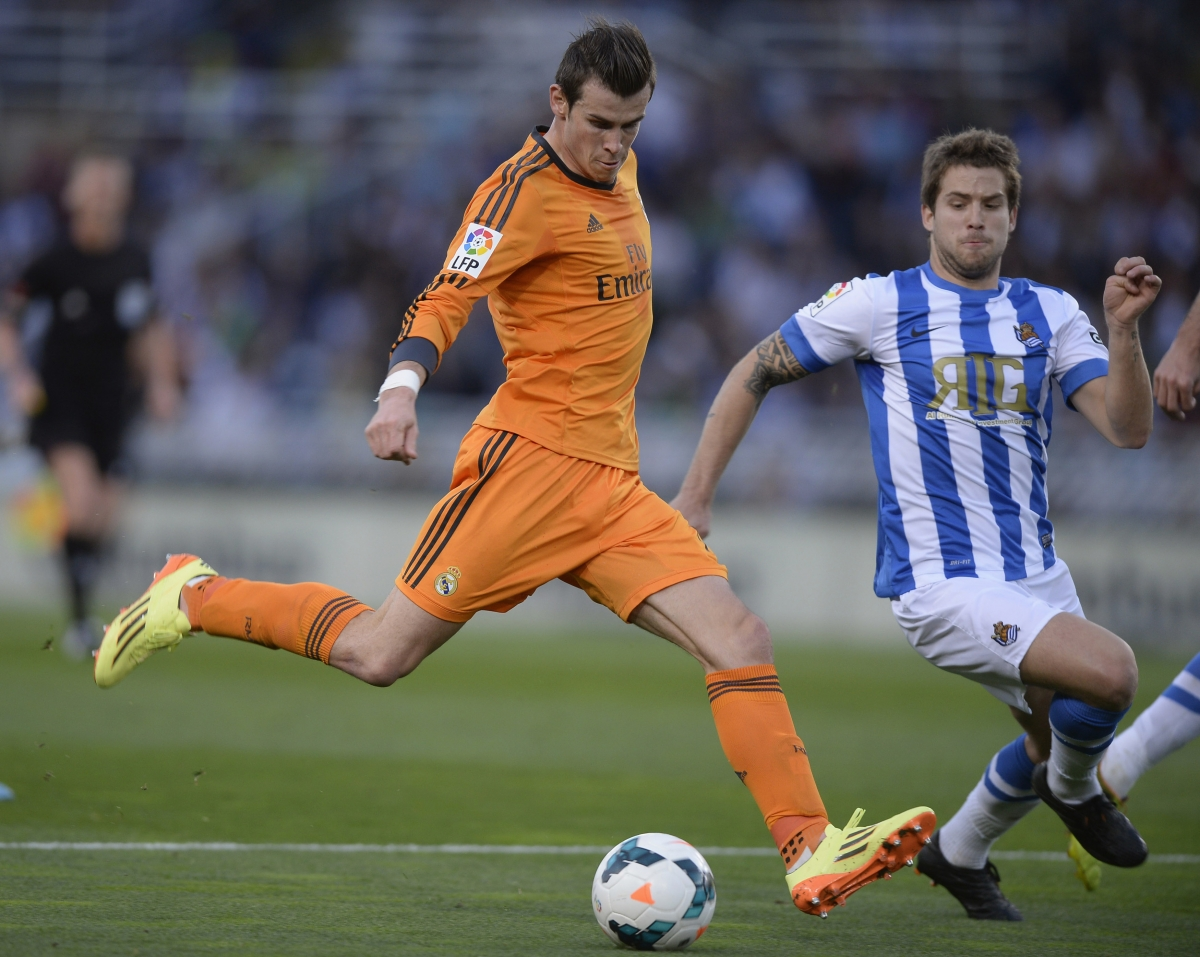 Real Madrid's Gareth Bale (L) shoots the ball past Real Sociedad's Inigo Martinez during their La Liga soccer match at Anoeta stadium in San Sebastian April 5, 2014.