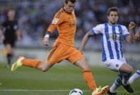 Real Madrid\'s Gareth Bale (L) shoots the ball past Real Sociedad\'s Inigo Martinez during their La Liga soccer match at Anoeta stadium in San Sebastian April 5, 2014.