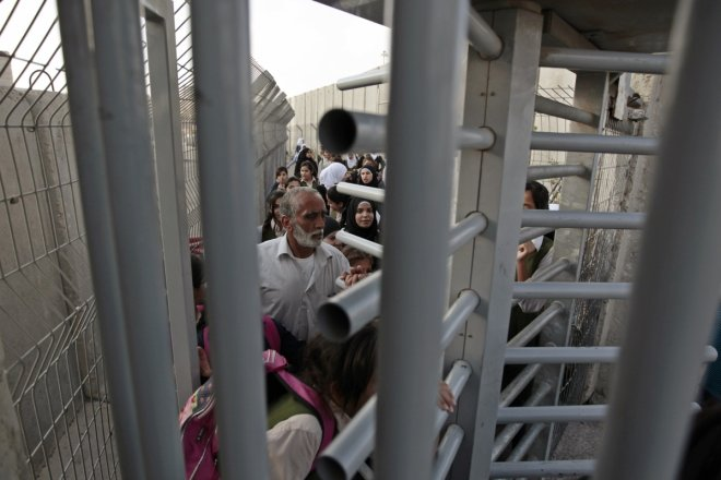 Palestinians wait to cross through an Israeli checkpoint as they enter Shuafat refugee camp in the West Bank near Jerusalem
