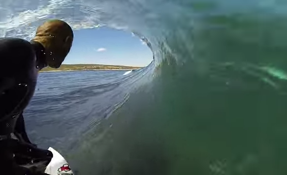 Kelly Slater surfing while a shark appears in the water