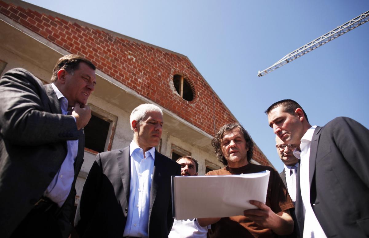Serb Republic President Milorad Dodik (L), former Serbian President Boris Tadic (2nd L) and Serbian film director Emir Kusturica (2nd R) look at blueprints of the construction project of Andricgrad in 2012