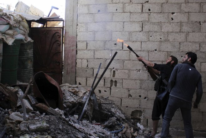 A rebel fighter fires during clashes with Syrian forces in eastern al-Ghouta, near Damascus