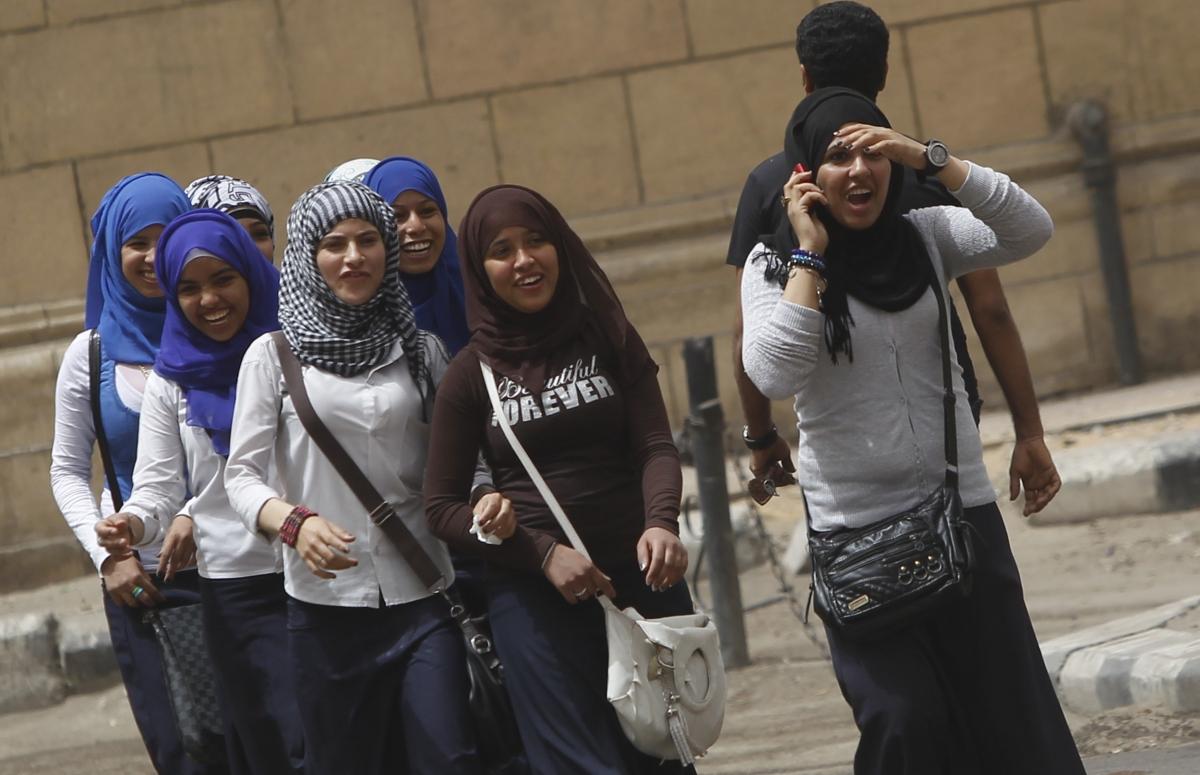 School girls walk on a street in Cairo