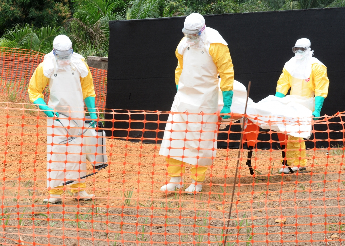 Caption:Staff of the 'Doctors without Borders' ('Medecin sans frontieres') medical aid organisation carry the body of a person killed by Ebola, at a center for victims of the Ebola virus in Guekedou, Guinea.