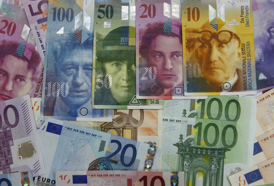 Varoius Euro banknotes lay next to various Swiss Franc notes in this picture illustration at a bank in Warsaw
