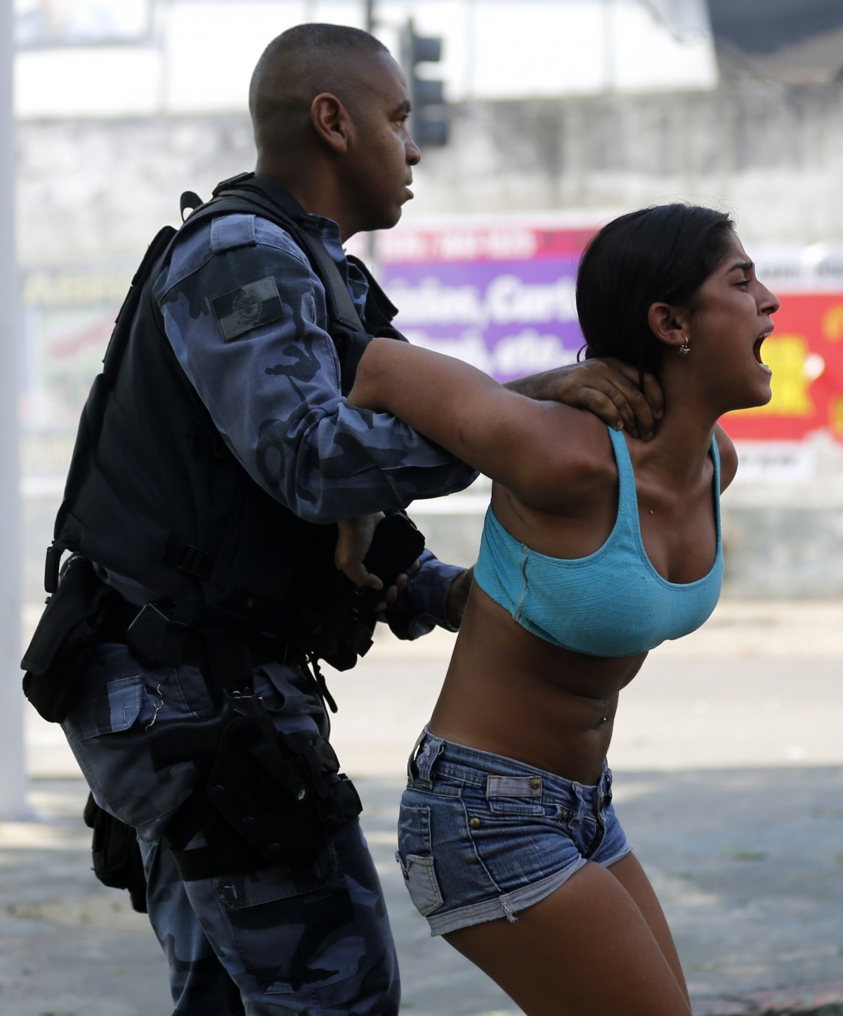 A riot policeman arrests a demonstrator from a favela in Rio de Janeiro