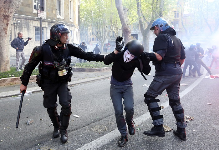 A demonstrator is detained by policemen during a protest against austerity measures in Rome.