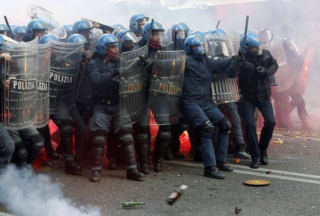 Riot police face off with protesters throwing bottles and flares during an anti-austerity protest in Rome.
