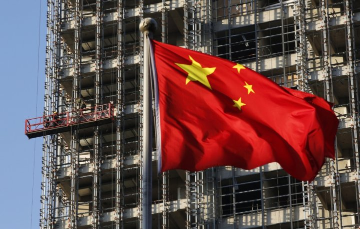 A Chinese national flag flutters at a construction site for a new residence complex in Beijing