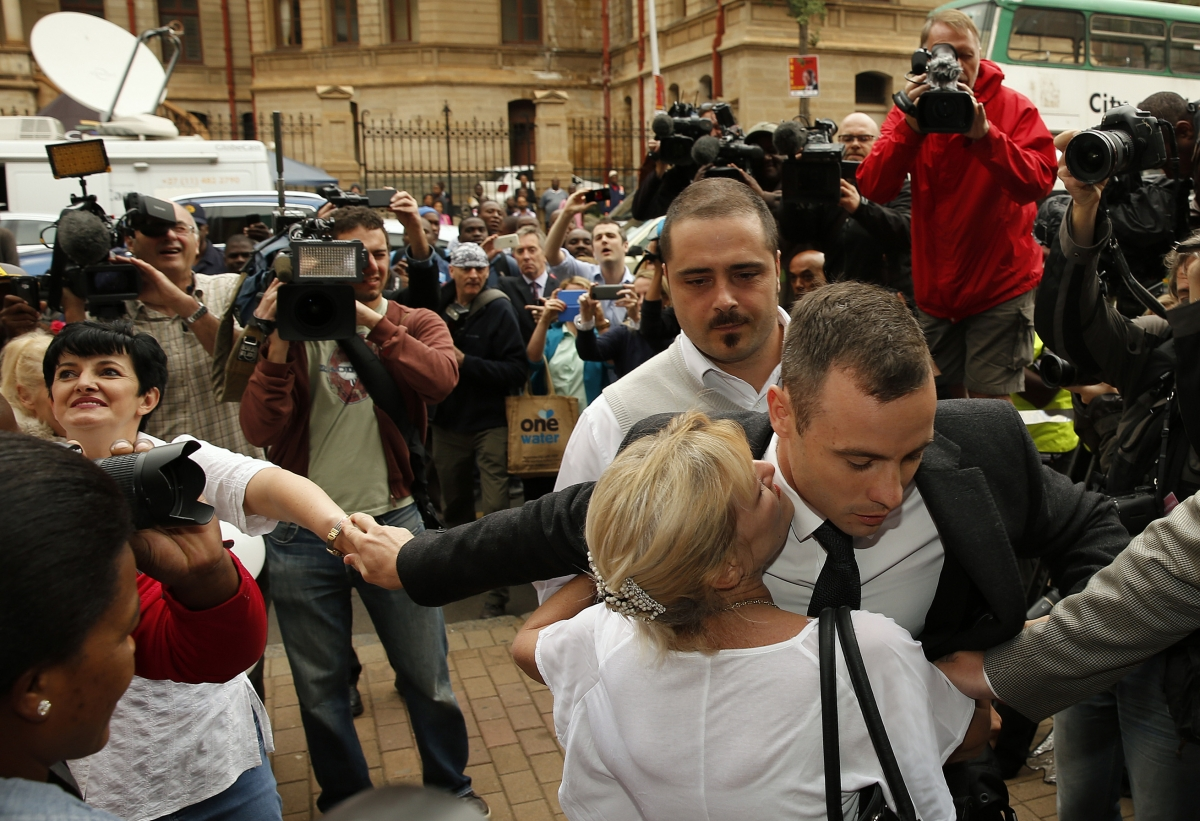 Oscar Pistorius embraced by blonde woman as he arrives at his murder trial