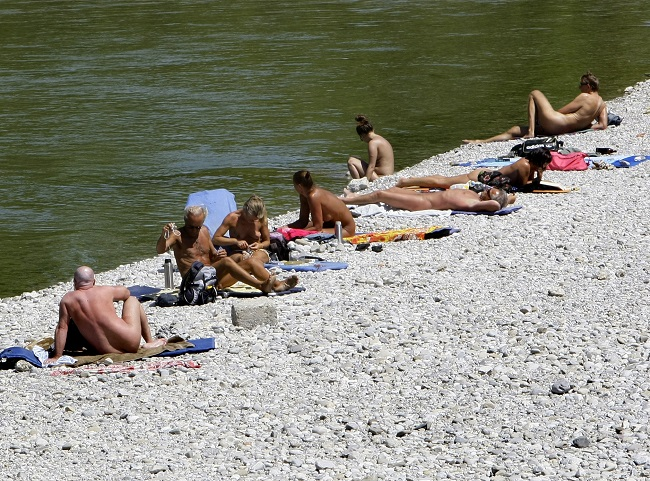 People sunbathe next to the Isar river in downtown Munich.