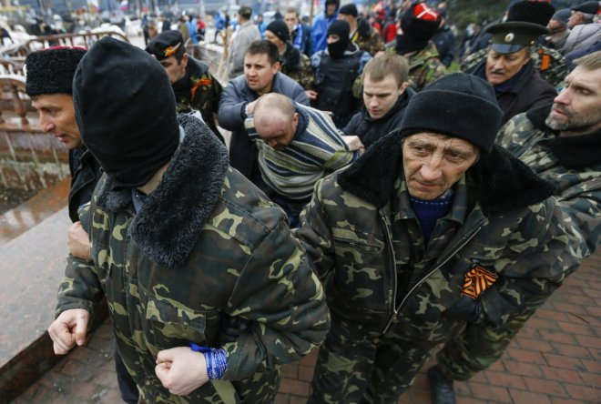 Pro-Russian protesters escort a man detained yesterday, who they said provoked them by trying to sell a pistol, near the seized office of the SBU state security service in Luhansk, in eastern Ukraine