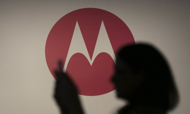 A woman takes a picture in front of a Motorola logo