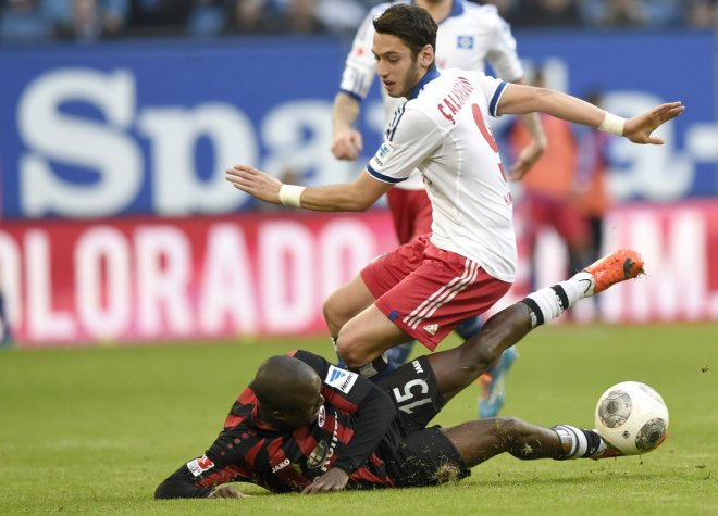 Hamburg SV's Hakan Calhanoglu (top) and Eintracht Frankfurt's Constant Djakpa (L) fight for the ball during their German Bundesliga first division soccer match in Hamburg, March 8, 2014.