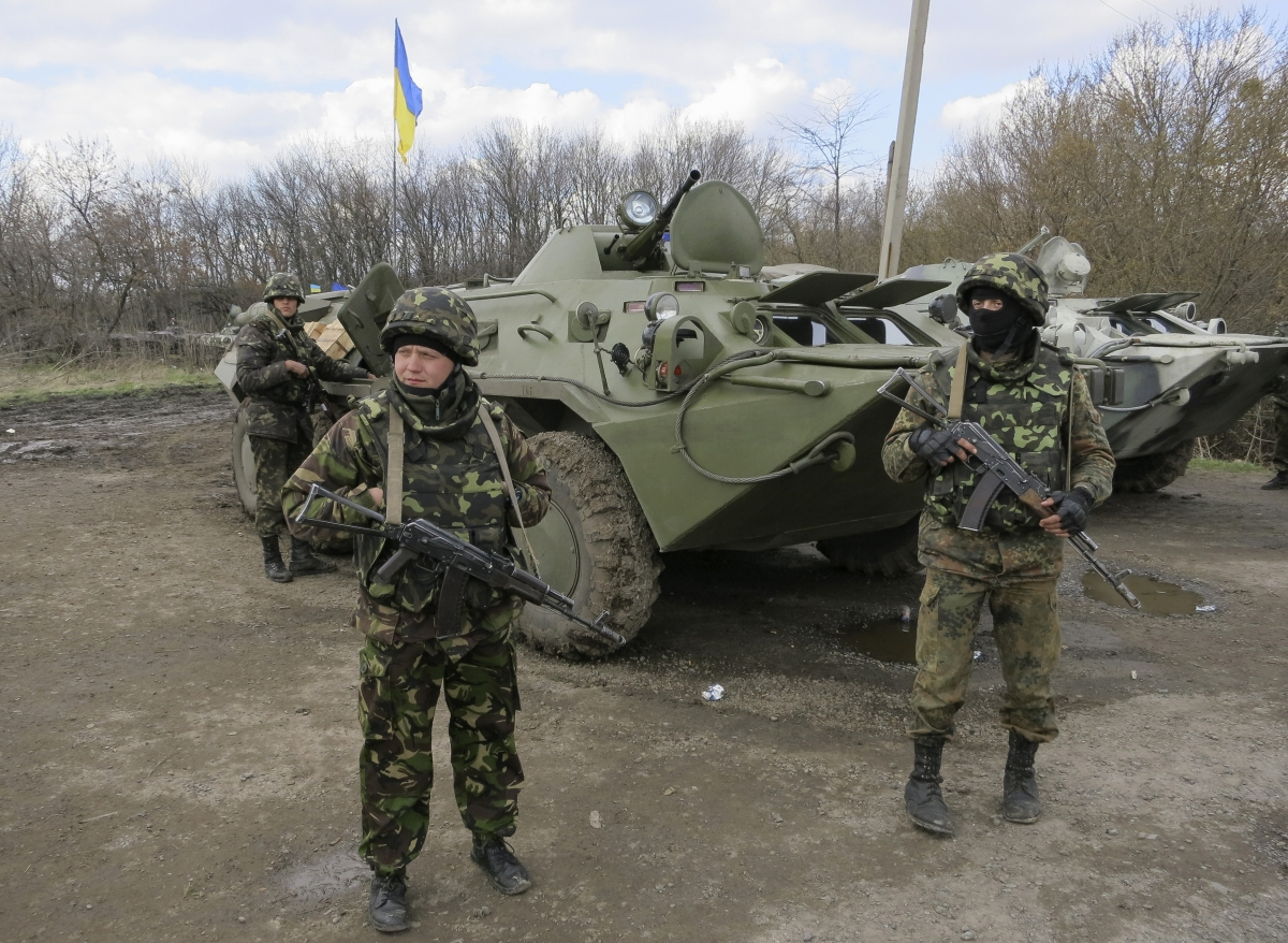 Ukrainian soldiers are seen near armored personnel carriers at a checkpoint near the town of Izium in Eastern Ukraine