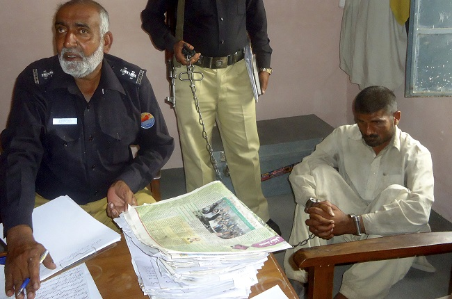 Mohammad Arif, 35, (R) sits in a police custody at a police station, in the town of Darya Khan in Bhakkar District