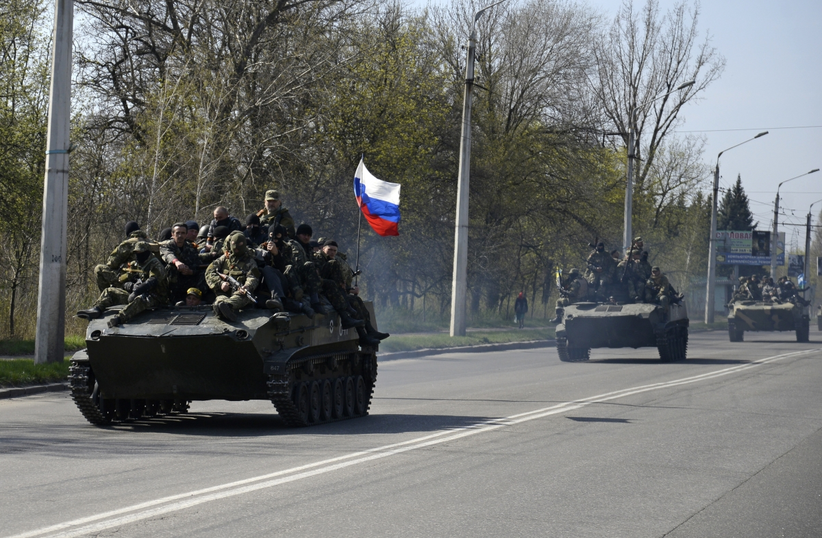 Armed men, wearing black and orange ribbons of St. George - a symbol widely associated with pro-Russian protests in Ukraine, drive an airborne combat vehicle (L) with a Russian flag seen on the top, outside Kramatorsk